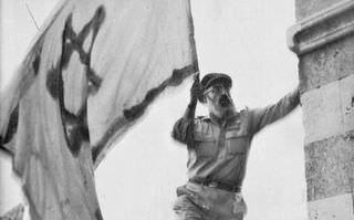 Rabbi Goren holding the Israeli flag as he liberated Hebron in June of 1967