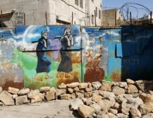 (Photo: Mural on a wall in Hebron's Old City depicting the scouts carrying grapes.)