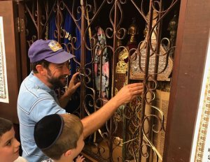 Rav Simcha Hochbaum,shows ancient torah scroll in Abraham Avinu synagogue