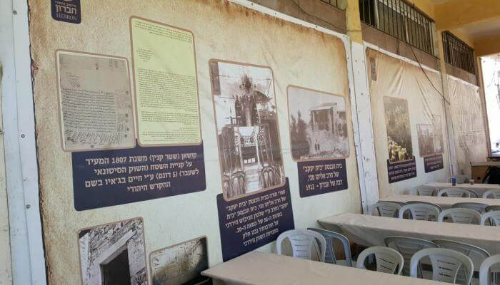 (PHOTO: A copy of the 1807 deed and other historic photos are displayed on the walls of the empty Mitzpe Shalhevet building. Temporary tables and chair are set up for the Shabbat Chayei Sarah weekend.)